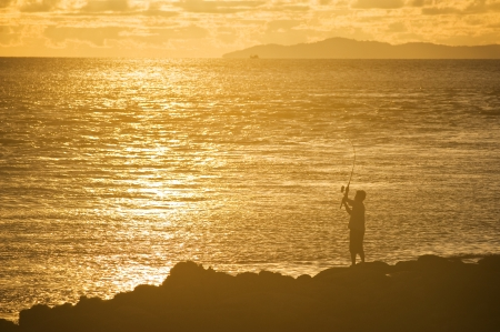 A man is fishing in evening and gold sunset background  Stock Photo