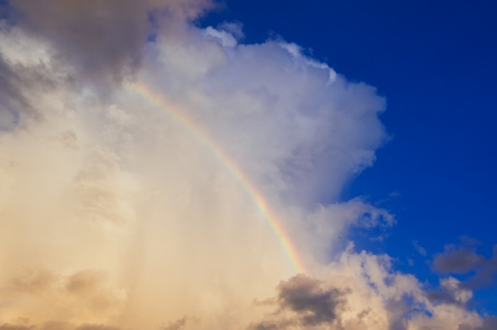 A photography of a white cloud in the evening sun with a rainbow