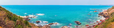 A view of the turquise color of the sea from above, a delightful landscape with rocks and ocean. Walk along the Querim Beach Arambol trail, Goa, India, active holidays in paradise resorts. Stock Photo