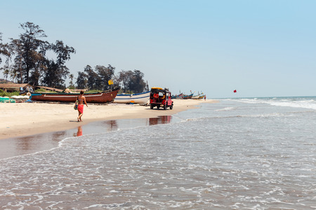 View of sandy tropical beach Mandrem Beach with palm trees and boats on the shoreline. The paradise resort of Goa on the ocean, India on April 2, 2017, the closure of the tourist season.