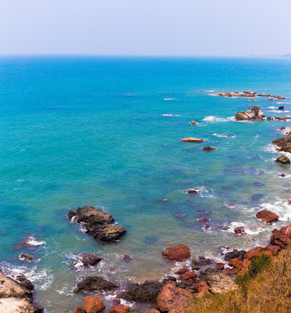 Tropical sea view with trees and rocks in the background, the coast of the Arabian Sea, Goa, India, beach Querim Beach. Shoreline with clear undulating sea water of the ocean on a sandy beach on a sunny day. Stock Photo