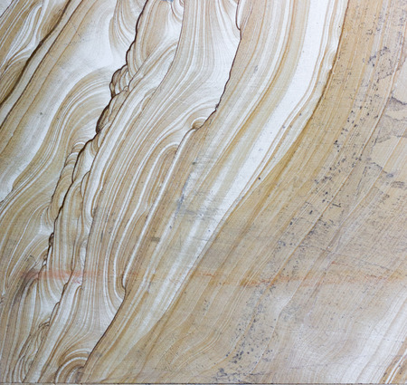 Background surface of decorative stone, sandstone with lines, volcanic material for cladding. The texture of a rocky plate with mystical patterns similar to waves, veins and clouds. Imagens