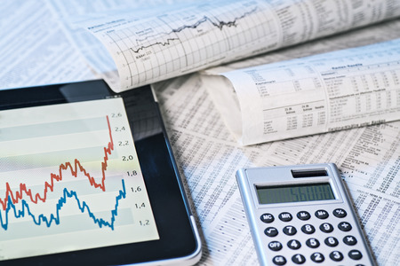 financial services: Stock prices on tablet computer and in the newspaper Stock Photo