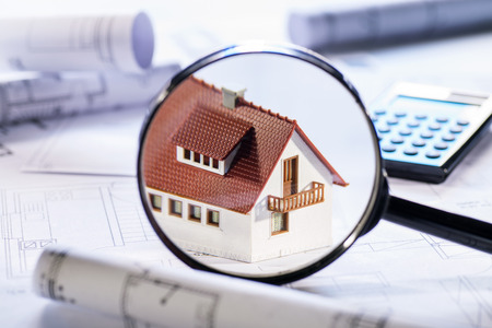 Magnifier focuses a house standing on blueprints Stock Photo