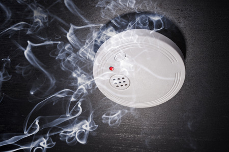 fire alarm: Smoke detector in the smoke of a fire