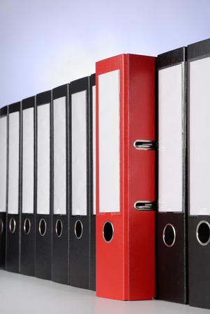 registros contables: Un aglutinante anillo rojo entre una serie de archivos de negros Foto de archivo