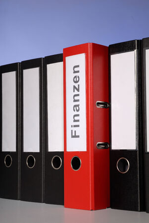 Red folder with the inscription   FinanzenFinance   between a series of black ring binders  photo