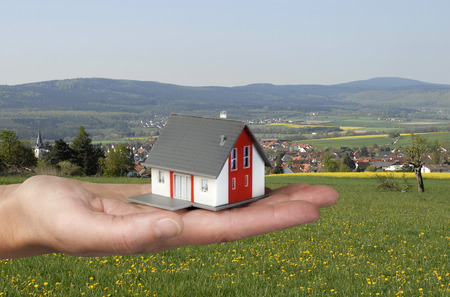 private insurance: Hand holding an architectural model in front of a rural landscape  Stock Photo