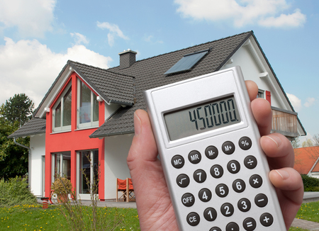 state owned: Calculator with high sum in the display in front of a house Stock Photo