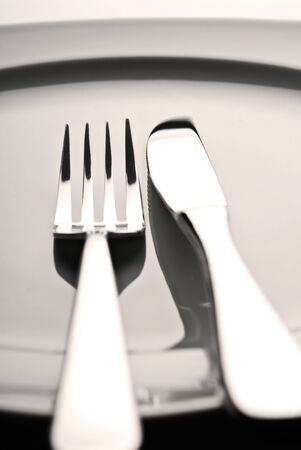 Fork and knife lying on an empty plate