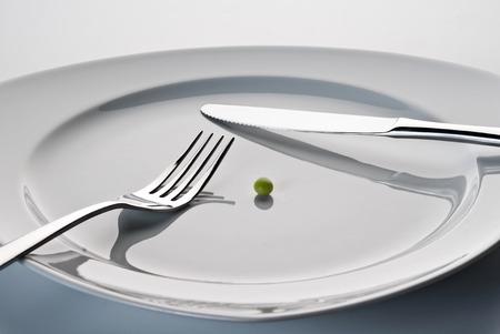 Plaat met mes, vork en een erwt Stockfoto