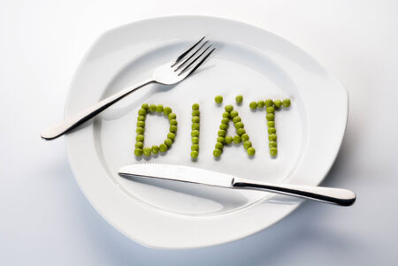 Peas forming the word diet on a plate with cutlery