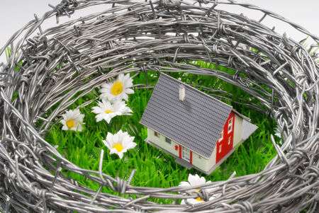 responsibly: A house on a green field surrounded by barbed wire