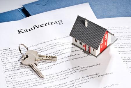 Architektur-Modell mit einem Kaufvertrag und die Schlüssel