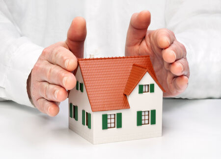enclose: Hands protectively enclose an architectural model Stock Photo