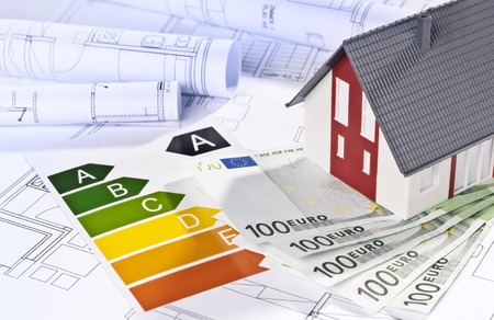 Architectural model, architectural plans, energy efficiency labels and money Stock Photo