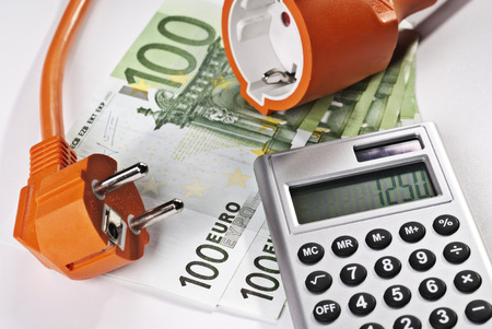 High electricity costs symbolized by connector, calculator and money Banque d'images