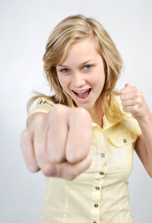 Young blonde woman defends herself with her fists