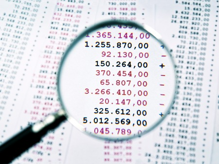 insolvency: Magnifying glass focused an invoice with negative numbers Stock Photo
