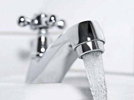 Trinkwasser fließt aus einer verchromten Wasserhahn Lizenzfreie Bilder