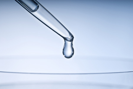 Pipette with drop and petri dish  Stock Photo