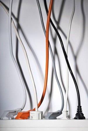 self indulgence: Power strip and power cables leading vertically upwards  Stock Photo