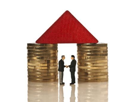 握手をコインにかかっている赤い屋根の下で 2 人のビジネスマン
