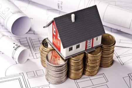 Architekturmodell auf Stapel von Münzen Lizenzfreie Bilder
