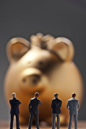 bank owned: Business men looking on an oversized piggy bank