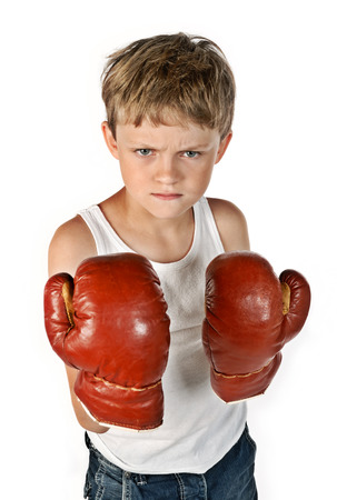 boy boxing: Little boy with boxing gloves is ready to fight and looks very angry  Stock Photo