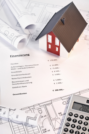 House, blueprints, calculator and a paper with the german word  Finanzierung  and a listing of various costs in german and amounts in €  photo