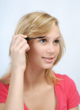Blonde girl putting mascara on