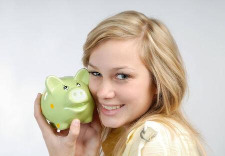 Beautiful blonde girl fondles a piggy bank  Stock Photo