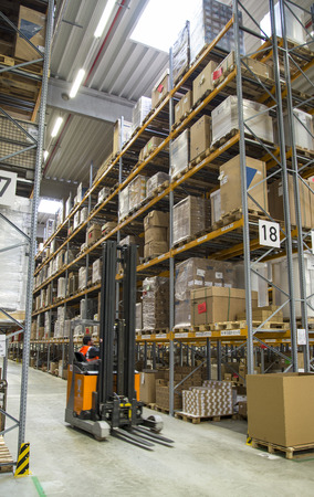 A forklift in front of a high shelf in a warehouse  Standard-Bild