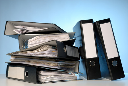 A pile of file folders on a desk. Stock Photo