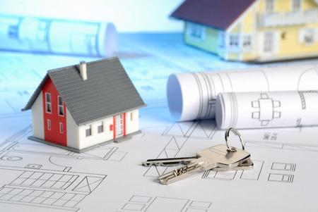 Zwei Häuser mit Blaupausen und Schlüssel