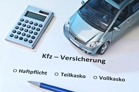 """Auto-, Taschenrechner und Stift auf einem Papier mit dem Wort Deutsch """"Kfz-Versicherung"""" für Kfz-Versicherung und die Wahl der Haftpflicht, Teilkasko-oder Vollkaskoversicherung."""