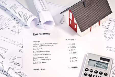 House, blueprints, calculator and a paper with the german word Finanzierung and a listing of various costs in german and amounts in €.