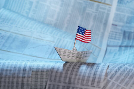 debt management: Paper boat with US flag shipping on financial news. Stock Photo