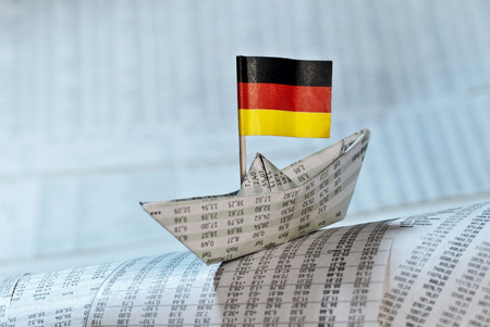 Paper boat with German flag shipping on stock market news. Stock Photo