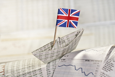 Paper ship with British flag on stock market news. photo