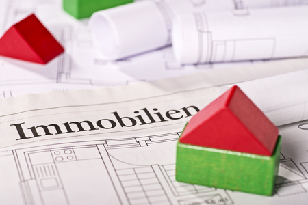 immobilien: Small building blocks house on blueprints with the german word Immobilien