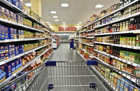 leer: An empty cart between shelves in the supermarket.