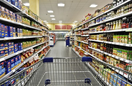 An empty cart between shelves in the supermarket.