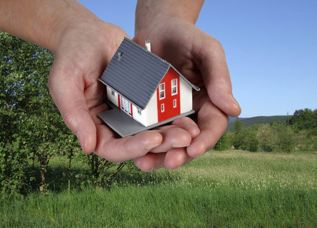 House on hands in front of a green landscape