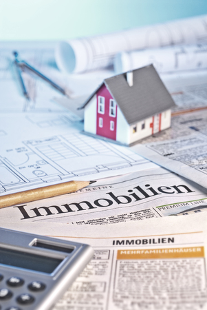 architectural firm: House with blueprints, calculator and a newspaper with real estate offers on which the german word  Immobilien  is to be read