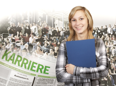 Beautiful blonde girl in front of a large group of young people with a newspaper on which the german word  Karriere  is to be read  In the newspaper job advertisements are to be seen  photo