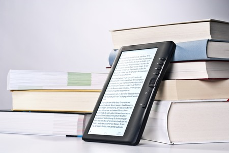 EBook leaning against a stack of printed books