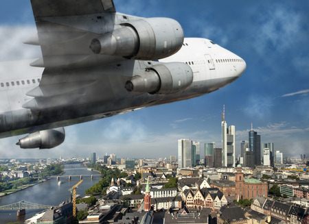 A large passenger aircraft flies over the German city Frankfurt  Stock Photo