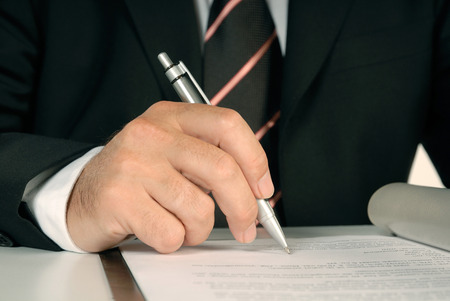 acknowledge: Close up of a businessman signing a document